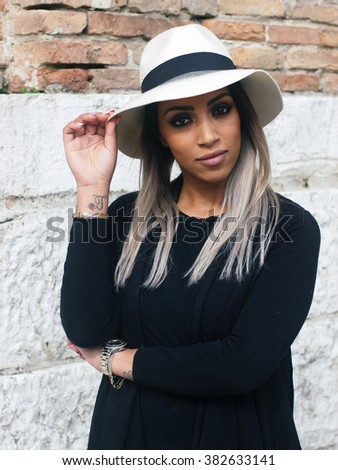 Spring outfit - Portrait of a young pretty woman with granny hairstyle, wearing black jacket and sweater and hat