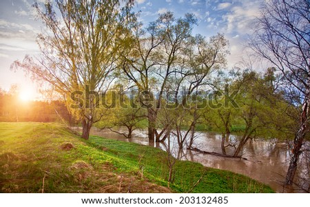 Spring panorama with the river in morning light - stock photo