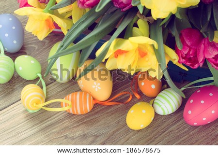 spring pink  tulips and yellow daffodil flowers with easter eggs - stock photo