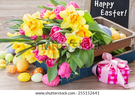 spring pink  tulips and yellow daffodil flowers with easter eggs and gift box - stock photo