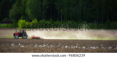 Spring planting time, tractor working on the field. - stock photo