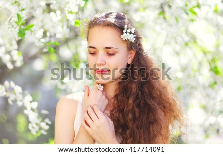 Spring portrait beautiful young girl with curly hair in flowering garden