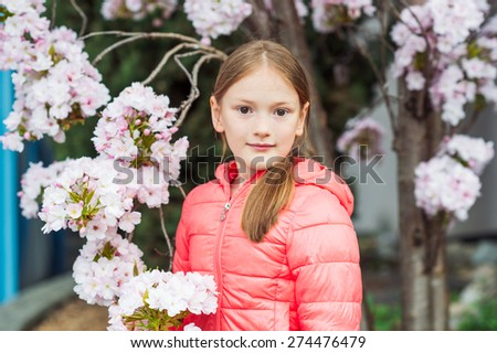 Spring portrait of a pretty little girl of 7 years old, wearing coral jacket, standing between branches of a blooming tree - stock photo
