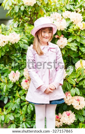 Spring portrait of adorable little girl, wearing rain hat and coat - stock photo