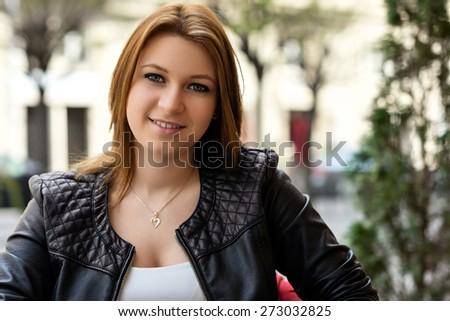 Spring portrait of an attractive young woman smiling friendly - stock photo
