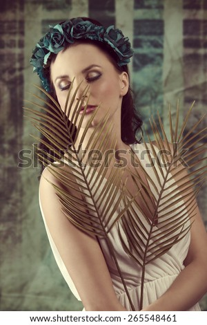 spring portrait of charming brunette woman with long hair, stylish make-up, flowers on head and palm leafs in the hand. Wearing white dress, romantic expression  - stock photo