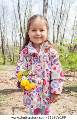 Spring Portrait of happy little girl with flowers in nature.