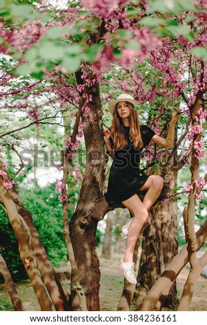 Spring portrait of young girl around blooming trees. Enjoying the spring.