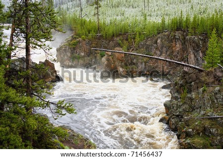 Spring rain and snow fill the Firehole River, Yellowstone National Park. - stock photo