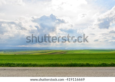 Spring road in the Romanian villages after a thunderstorm in the evening. Asphalt road through the green field and clouds on blue sky in the evening.
