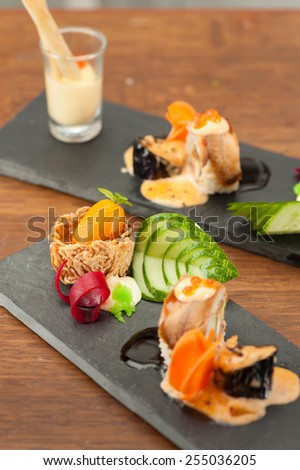 Spring roll with seaweed and Mentaiko served with mayo, Grilled eggplant with Scallop, Tako tempura roll and Namasu Kabayaki, Kumquat stuffed with smoked duck and mash potato in noodle nest - stock photo