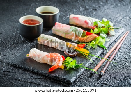 Spring rolls with vegetables, seafood and sauce - stock photo