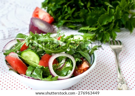 Spring salad with fresh lettuce rukolla, tomato, cucumber, radish, onion kolechekkrasnogo, dill, parsley, seasoned with sunflower oil in a bowl on a white background