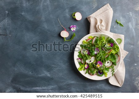 Spring salad with radishes, edible flower and sauce, selective focus