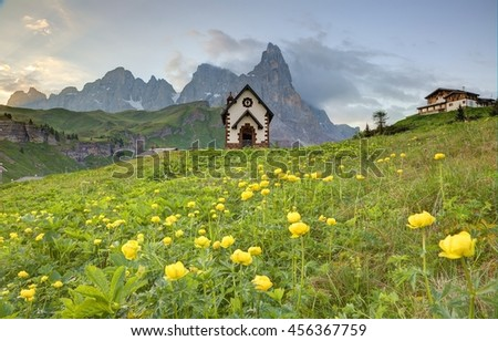 Spring scenery of Dolomites with view of a lovely church at the foothills of rugged mountain peaks ( Cimon della Pala ) under dramatic dawning sky in Passo Rolle, Dolomiti, South Tyrol, Italy, Europe - stock photo
