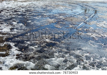 Spring slush. Ground covered with thawing snow and car trace. Blue sky reflected in water. - stock photo