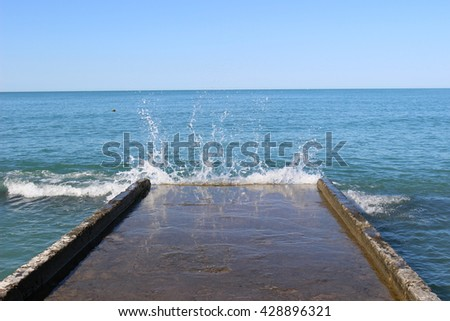 Spring, summer, travel, vacation and holidays concept - pier in a spray of water, black sea.