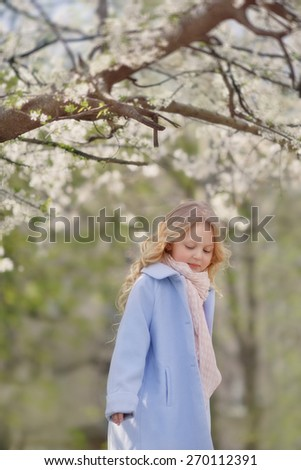 spring sunny day blond girl in blue coat in the lush garden - stock photo