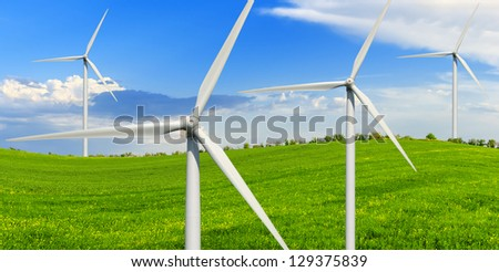Spring sunny day on a green meadow with wind power generators. - stock photo