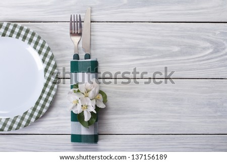 Spring table setting. Plate and cutlery decorated with flowers of apple on a wooden table. Top view. - stock photo