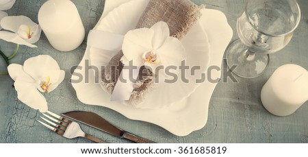 Spring table setting with orchid decorations, candles, wineglass on a gray background. Top view. Tinted.  - stock photo