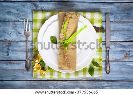 Spring Table setting with white plate and vintage silverware at wooden table. Top view. - stock photo