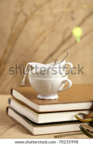 spring tea break, tea cups with diaries and twigs, shallow dof - stock photo