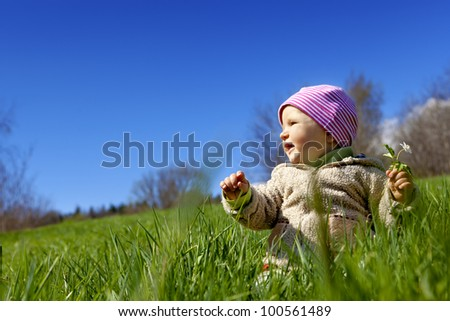 Spring. The little baby breaks up the flowers in the meadow. Sitting on the grass, holding a white flower in her hand, looking sideways at the sun. - stock photo