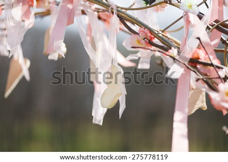 Spring tree in pastel pink blossom with wedding decoration - ribbons and hearts - stock photo