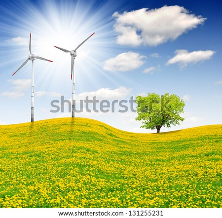 Spring tree on dandelions field with wind turbines - stock photo