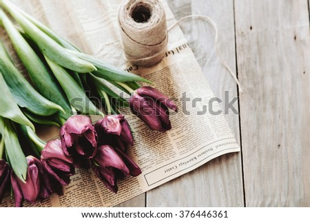 Spring tulips flowers wrapped in craft paper and twine on rough wooden table, selective focus, rustic eco style - stock photo