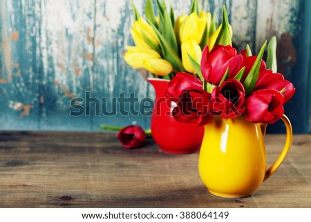 Spring tulips in vases  on wooden table - spring, easter or gardening concept - stock photo