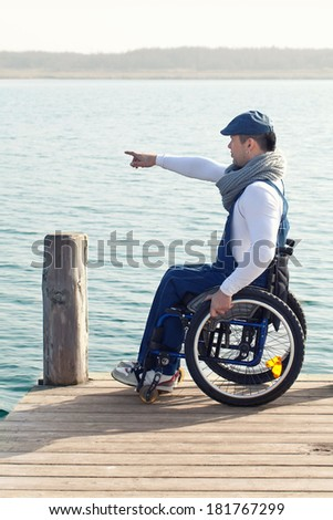 spring vacation: man in wheelchair enjoying outdoors beach  - stock photo