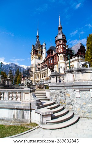 Spring view of Peles Castle with snow Bucegi Mountains in the background, Sinaia, Romania - stock photo