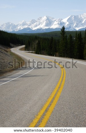 Spring view of rocky mountain and winding highway in the kananaskis country, alberta, canada - stock photo