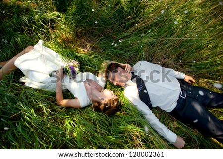 spring wedding theme, young couple in love, men and women lying on green grass and kissing. - stock photo