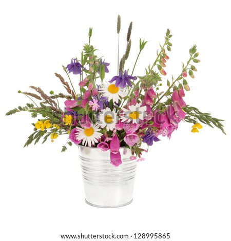 Spring wildflower and grasses arrangement in a stainless steel pot over white background.