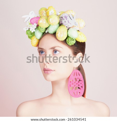 Spring Woman. Beauty model girl with colorful flowers. Easter Hair Style. Beautiful Lady with easter eggs on her head. Easter Woman.Portrait of Beautiful Model with Colorful Eggs - stock photo