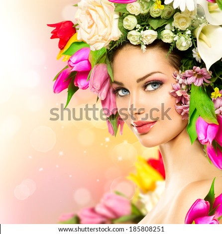 Spring Woman. Beauty Summer model girl with colorful flowers. Flowers Hair Style. Beautiful Lady with Blooming flowers on her head. Nature Hairstyle. Holiday Fashion Makeup. Make up - stock photo