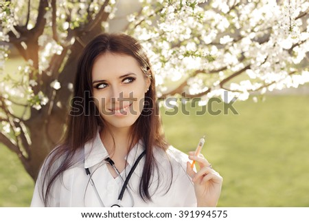 Spring Woman Doctor Smiling and Holding Vaccine Syringe - Portrait of female medical professional with allergy immunization remedy  in springtime   - stock photo