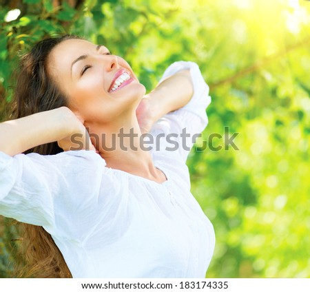 Spring Woman enjoying nature. Beautiful Young Woman Outdoors. Healthy Smiling Girl in the Green Park. Sunny day  - stock photo