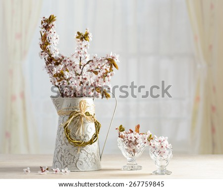 Springtime blossom in vase and antique glasses  - stock photo