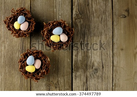 Springtime chocolate nests filled with candy eggs on a rustic wood background - stock photo