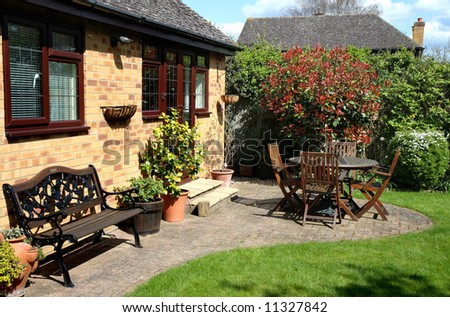 Springtime in an back garden in England with seating and Patio area - stock photo