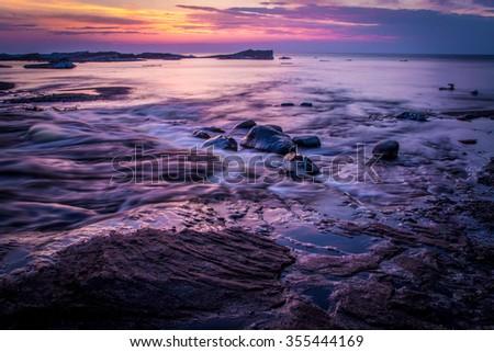 Springtime On The Shores Of Lake Superior. The sunsets on the shores of Lake Superior while icebergs float on the horizon. Pictured Rocks National Lakeshore. Munising, Michigan. - stock photo