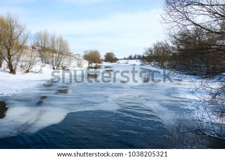 Springtime.Sunny landscape with  trees growing on the bank of river.Melting snow and ice.White clouds in spring blue sky.River Upa in Tula region,Russia.