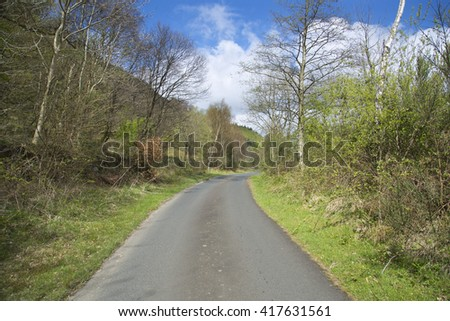 Springtime view of a small remote unused single track road running through a forest near  Ben Lomond in the sunshine beside Loch Lomond in Scotland UK with blue skies and storm clouds