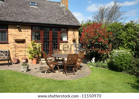 Springtime View Of An English Country Garden With Patio And Seating Area And  Pet Cat