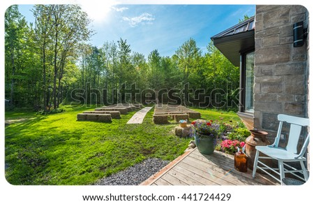 Springtime woodlot lawn, a chair on the porch, baskets, wagon wheels, a chair, hay benches, flowers, decorations & sunny day for an outdoor country, back yard wedding.  - stock photo