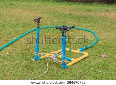 sprinkler in watering the green lawn. - stock photo